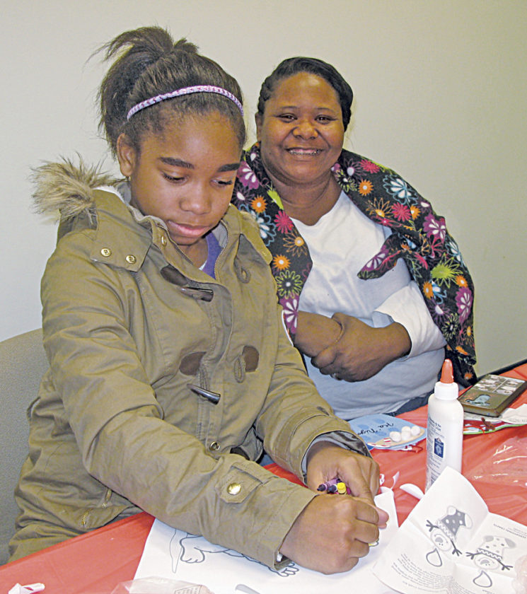 Photo by Jeffrey Saulton Keisha Ford, left, of Belpre, works on an entry for the Sheetz Coloring Contest in the Judge Black Annex during the 2017 Winterfest as her mother, Niyah Ford, right, watches.