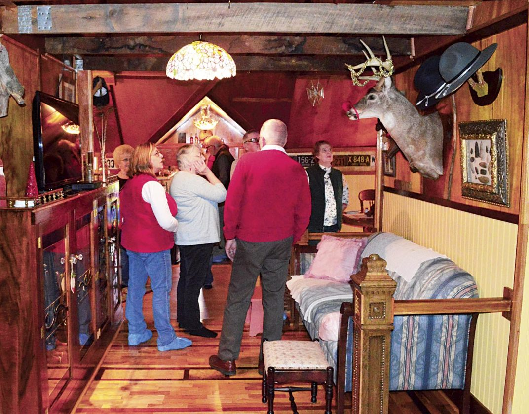 Photo by Doug Loyer Lowell Mayor Steve Weber welcomes tour goers to the attic which serves as his man-cave.