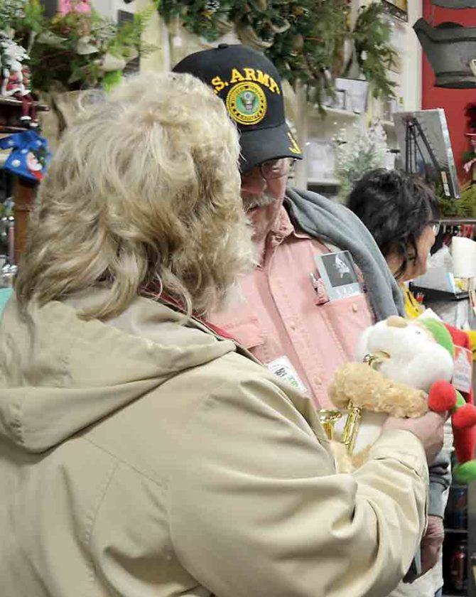 "Andy and Rita Molvie check out a saxophone-playing stuffed toy as it toodles out a jazzy version of ""Have Yourself a Merry Little Christmas."" The Marietta couple were touring A Unique Flower & Gift Shop on Front Street during the Monday night Cash Mob set up the first Monday of each month by Marietta Main Street. (Photo by Michael Kelly)"