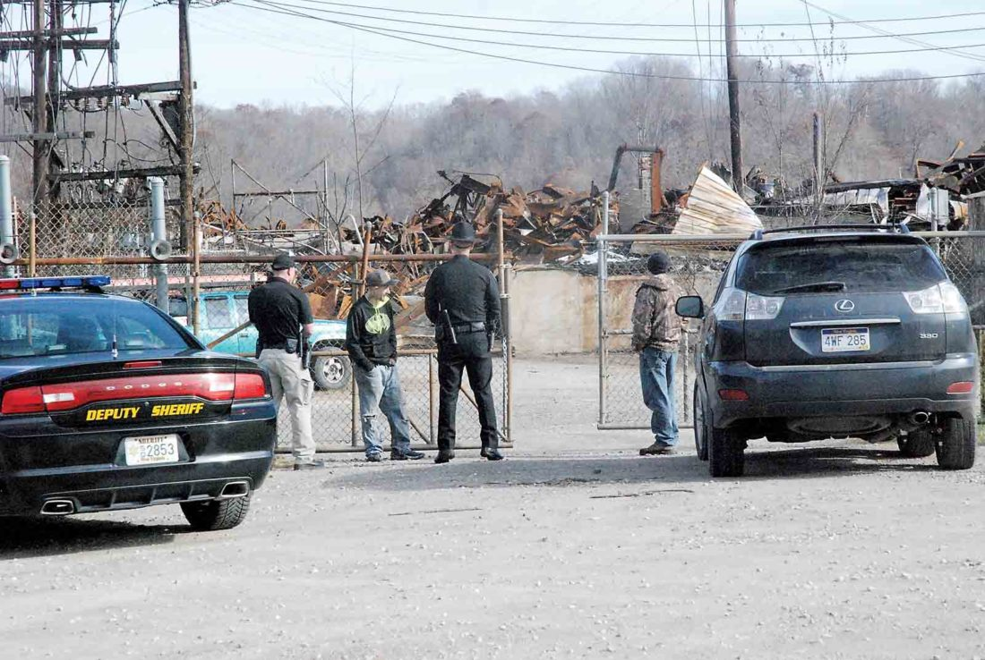 Parkersburg resident Aaron Wayne Callihan, second from left, talks with Wood County Sheriff's deputies and an employee at the IEI plastics site, right, after he was reportedly caught stealing copper from the site Monday morning. Callihan was cited for petit larceny and trespassing. (Photo by Evan Bevins)