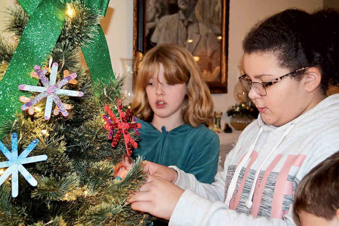 Harmar Elementary School fifth-graders Brianna Bowman, left, and Mikaiah Kinney, hang ornaments on a tree at the Henry Fearing House. (Photo by Kate York)