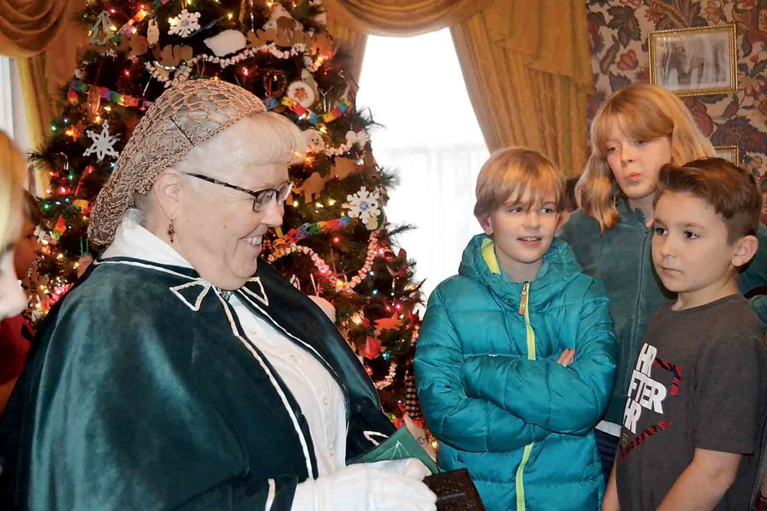 Washington County Historical Society member Mary Jo Hutchinson talks to a group of Harmar Elementary fifth-graders Tuesday at the Henry Fearing House Museum. Behind them is the home's folk art tree. (Photo by Kate York)