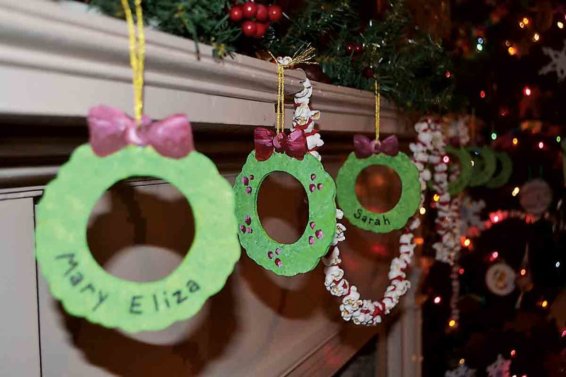 From a mantel at the Henry Fearing House hangs popcorn strands and wreaths featuring the names of the Fearing children. (Photo by Kate York)