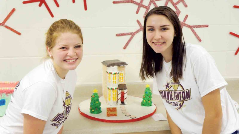 "Photo by Michael Erb Williamstown High School senior Bethany Wager, left, and sophomore Mara Rinehart, right, stand next to the gingerbread house they hope to submit to next week's 2017 Gingerbread Festival at the Blennerhassett Hotel. Their creation is the home featured on the show ""Full House,"" only decorated for Christmas and entirely edible."