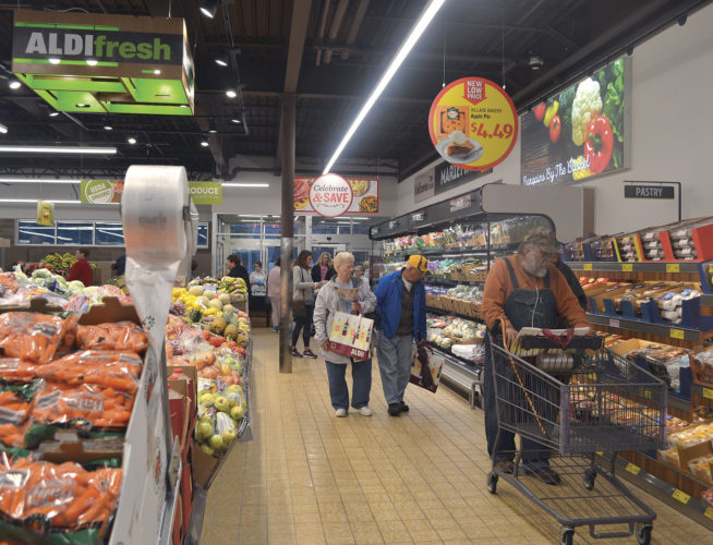 Photo by Erin E. O'Neill On Tuesday, people stream through the doors of the newly remodeled Aldi store, which includes a refrigerated produce section at the front of the store, a new idea for the company.