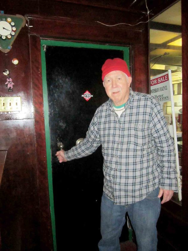 Photo by Wayne Towner Joe DeHaven stands beside the vault door that is a fixture in the Bankshot Pub, which served as a jewelry store in years past. DeHaven is closing the pub at the end of the year and plans to sell the building to  WesBanco, which will eventually demolish it.