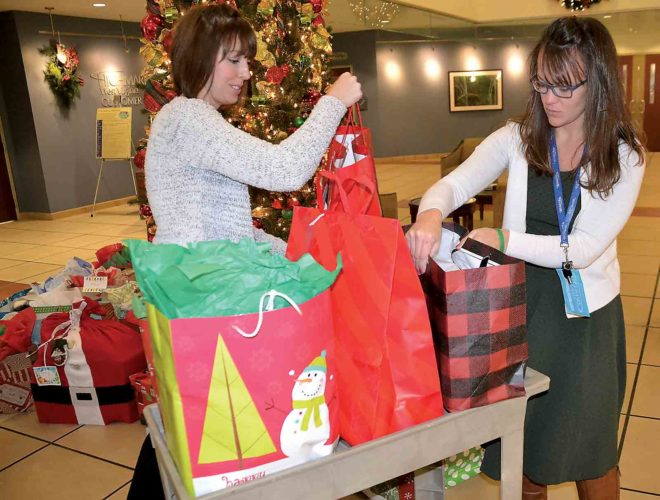Photo by Brett Dunlap Kristy Cramlet and Meggan Merritt of Highmark Blue Cross Blue Shield load gifts  Highmark employees got for 45 less-fortunate area seniors that will be distributed by the Salvation Army of Parkersburg through its Meals on Wheels program.