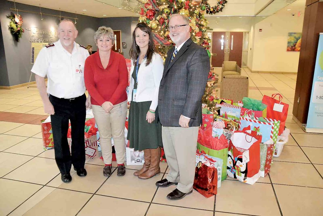 Photo by Brett Dunlap Major Matt Riley of the Salvation Army of Parkersburg; Terri Klingenberg, a senior enrollment and billing representative for Highmark; Highmark's Medicare Advantage Manager Meggan Merritt and Jim Fawcett, president of Highmark West Virginia, gathered at Highmark's Parkersburg office on Wednesday. Highmark employees got gifts for 45 less-fortunate area seniors through the Salvation Army's Meals on Wheels program and presented them to Riley for distribution.