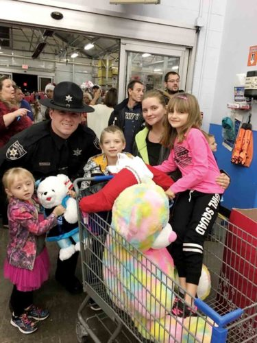 Photo provided Wood County Sheriff's Deputy Cody McClung with a few of the children who participated in the Shop with a Cop program at Wal-Mart in Wood County on Sunday.