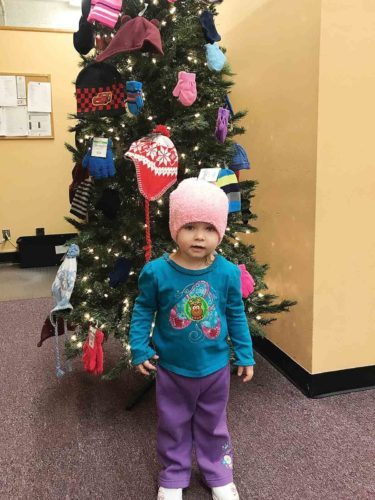 Photo Provided Lillian Webb, daughter of Melissa Webb, this year was the first child to pick from the Hat and Mitten Tree. The tree is sponsored by the Mid-Ohio Valley WIC.