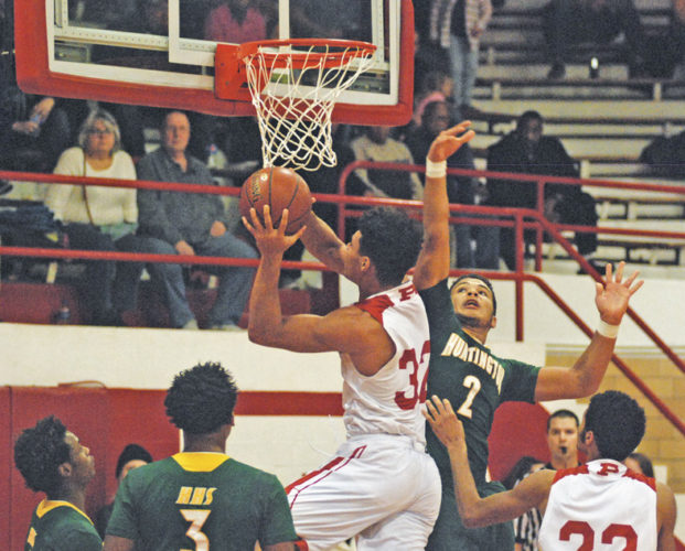 Parkersburg's Brenton Strange powers to the bucket for a field goal against the defense of Huntington's Bryce Damous during Friday night's game inside Memorial Fieldhouse. Photo by Jay W. Bennett.