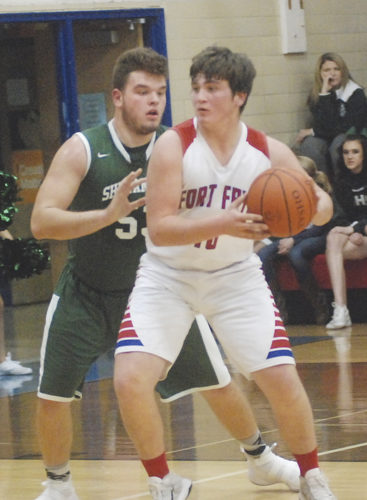 Fort Frye's Tyler Bradford (10) looks to pass as Shenandoah's Tanner Brown defends during a high school boys basketball game Friday night in Beverly. Photo by Jordan Holland.