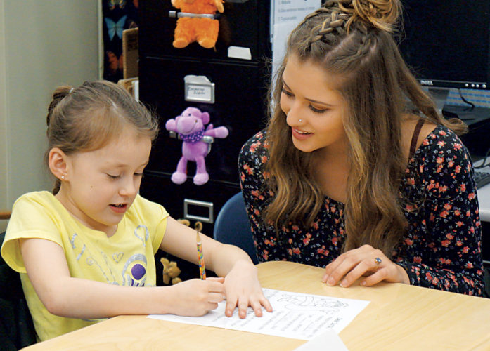 Photo by Michael Erb Martin Elementary School second-grader Christa Rector, left, makes changes to a letter to Santa Claus while getting advice from her pen-pal, Parkersburg South High School junior Hannah McKain, right, Tuesday at South.