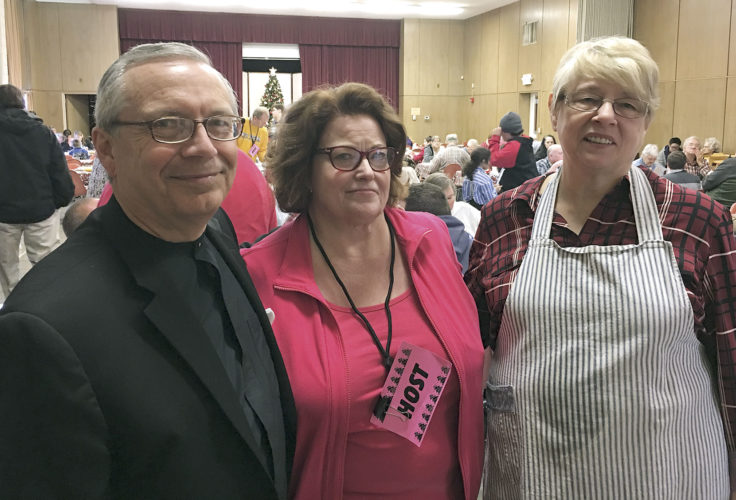 File Photo During last year's Community Christmas Dinner at First Presbyterian Church of Parkersburg, the Rev. Michael Seely, left, stands with dinner co-coordinators Sarah Townsend, center, and Debbie Karr, right.