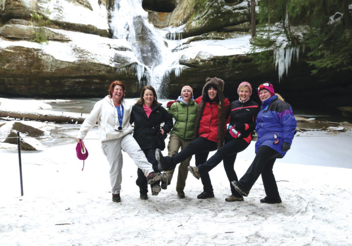 Photo submitted by Karen Raymore, executive director of Hocking Hills Tourism Association Women hike through Cedar Falls in the winter. Hocking Hills will offer several winter hikes this month.