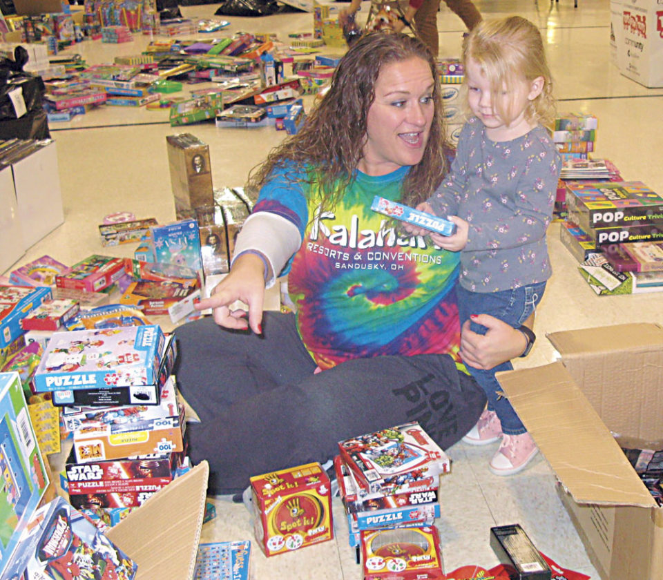 Photo by Jeffrey Saulton Tracy Wiggins, left, gets help in sorting puzzles from Amelia Noland.