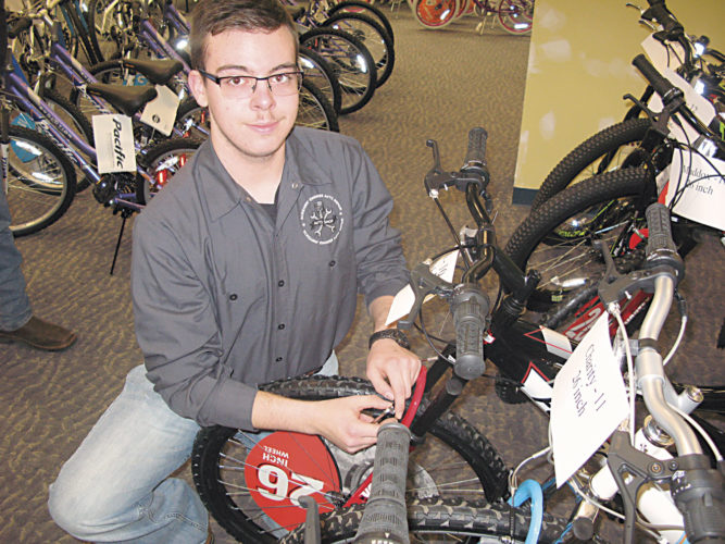 Photo by Jess Mancini Colten Bailey, a student at the Wood County Technical Center, makes final adjustments to a bicycle Saturday morning during the annual Bikes for Tykes program sponsored by the Wood County Deputy Sheriffs Association. Students assembled 100 bicycles.