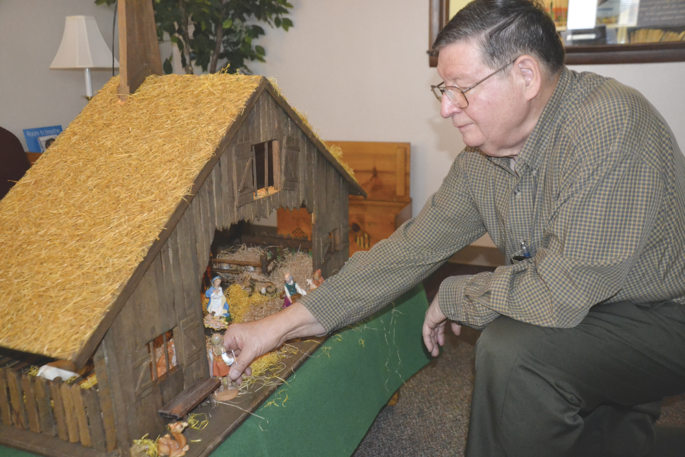 Photo by Brett Dunlap Dr. James F. Szarko places figures in a Nativity stable he built. The local dentist has built 27 such manger stables for a variety of people and places. This one is being presented to a local family this week.