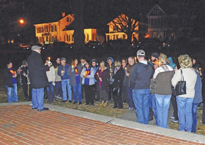 Photo by Doug Loyer Candles are lit during the Hope for the Holidays candlelight vigil in Marietta Sunday night.