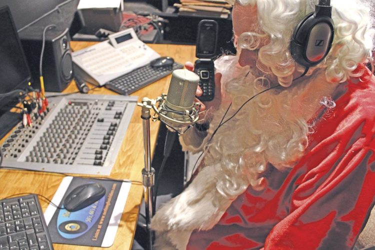 Photo Provided Santa at work in his studio making his live calls and recording the calls on CD.
