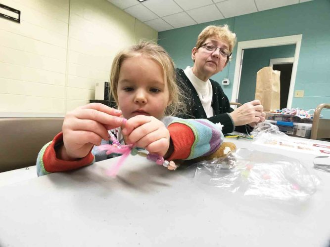 Photo by Janelle Patterson Sophia Morgenstern, 4, of Beverly, strings a pipecleaner snowflake through beads Wednesday during the craft portion of Story Time at Beverly's public library. Librarian Kay Erickson, right, looks on.