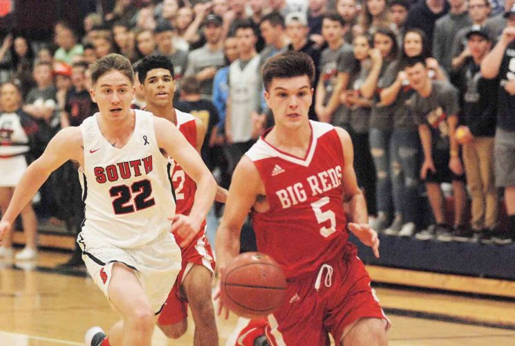 Parkersburg's Parker Miller drives to the basket while Parkersburg South's Shane Snider tries to run him down during the Patriots' 51-46 victory against the Big Reds. (Photo by Joseph Albright)
