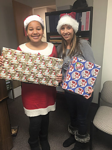 Photo Provided Aleatha Ellis, left, and Tabby McClung hold presents for children in the Secret Santa program.