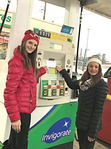 Photo Provided Jackson Middle School seventh-graders Lakyn Campbell and Jenna Carpenter leave a gift card at a Wood County business Saturday.