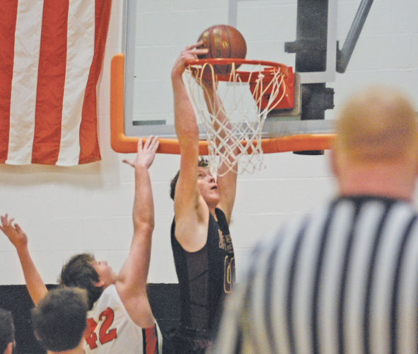 Williamstown's Cullen Cutright gets past Wirt County's Kyler Carper for a dunk during the second period of Wednesday's WCHS Holiday Tournaemnt in Elizabeth. The Yellowjackets defeated the Tigers, 61-47, and will take on Buffalo in today's 8 p.m. championship game. The host Tigers will face Wahama in the 6 p.m. consolation tilt. Photo by Jay W. Bennett.