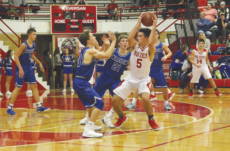 PHS's Parker Miller gets some serious defensive pressure from Warren's Seth Dennis, left, and Troy Huck during the Big Reds' 65-59 non-conference victory at Memorial Fieldhouse Thursday night. Miller led all scorers with 25 points. Photo by Tom Perry.