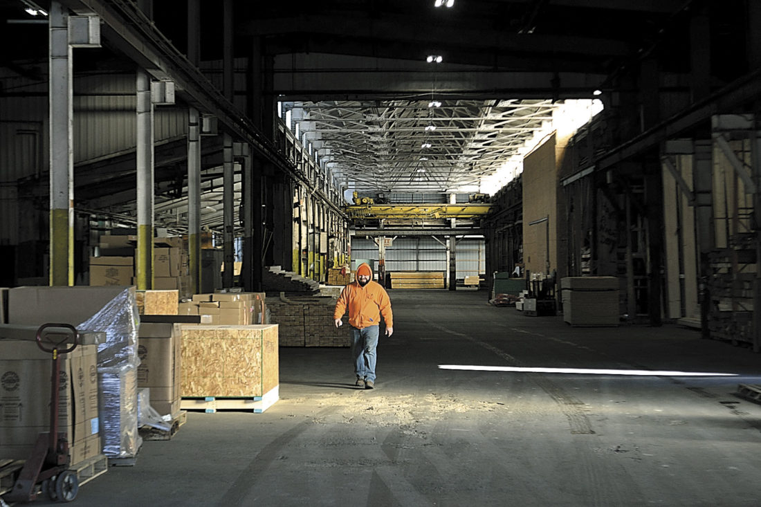 Photo by Michael Kelly A yard hand at Contractors Building Supply walks through the cavernous covered materials yard, where customers can drive through and have their orders loaded. The store is marking its 20th year in business next month.