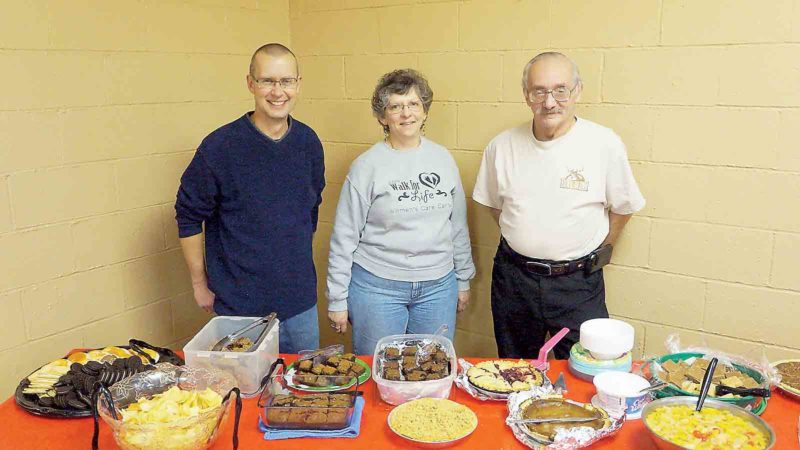 Baptist Temple Parkersburg Pastor Scott Wight, left, member Mary Foutty, center, and office assistant Dave Miller, right, stand next to a table of desserts Monday at the church's annual New Year's Day Dinner. (Photo by Michael Erb)