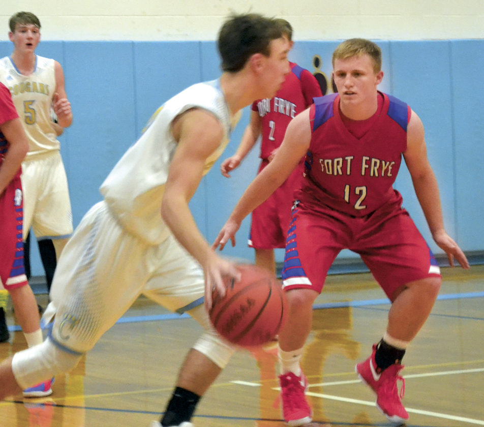 Fort Frye's Tate Engle (12) defends Froniter's Breckin Hoff dribbling during boys' basketball action Tuesday night. Photo by Ron Johnston