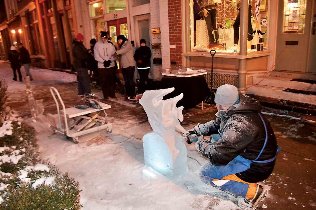 Photo by Michael Kelly With darkness falling on Front Street, Tyson Whistler works toward the finish of an ice sculpture in front of the Twisted Sisters Boutique on First Fridays in downtown Marietta.