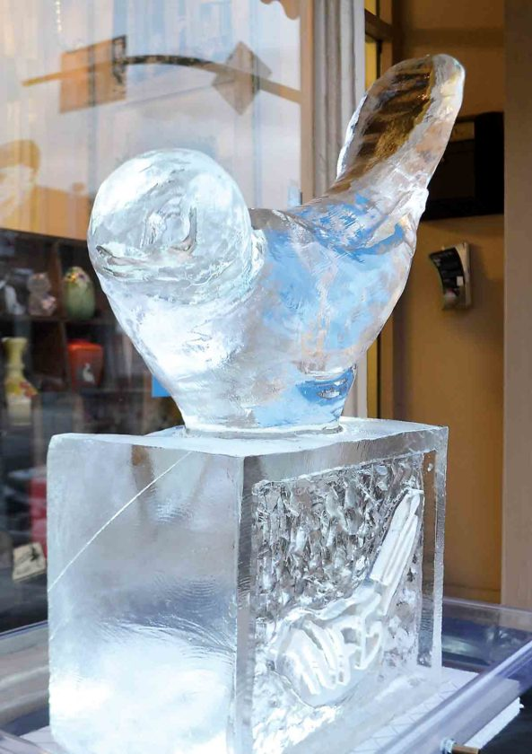 """Photo by Michael Kelly An ice sculpture by Tyson Whistler in front of the National Fenton Glass Society office on Front Street in downtown Marietta. Sculptor Tyson Whistler created the bird as a tribute to the """"Happiness Bird"""" mold done by Bill Fenton."""