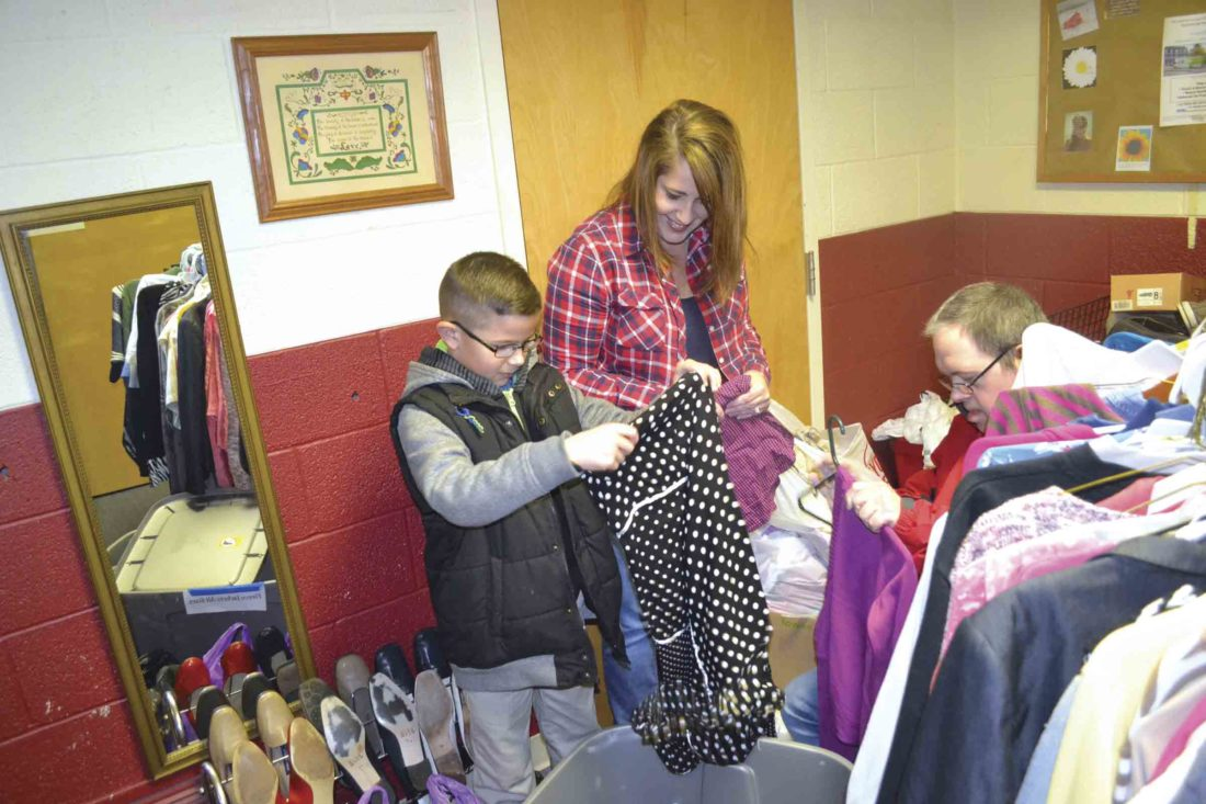 Photo by Erin O'Neill Volunteers Wyatt Bishman, left, Tara Wolfe, center, and Preston Hoff, seated right, sort through donations of clothes at the Salvation Army, 136 Front St. in Marietta. Bishman, 10, was helping as he waited to go to school. Marietta City Schools were on a two-hour delay Wednesday.