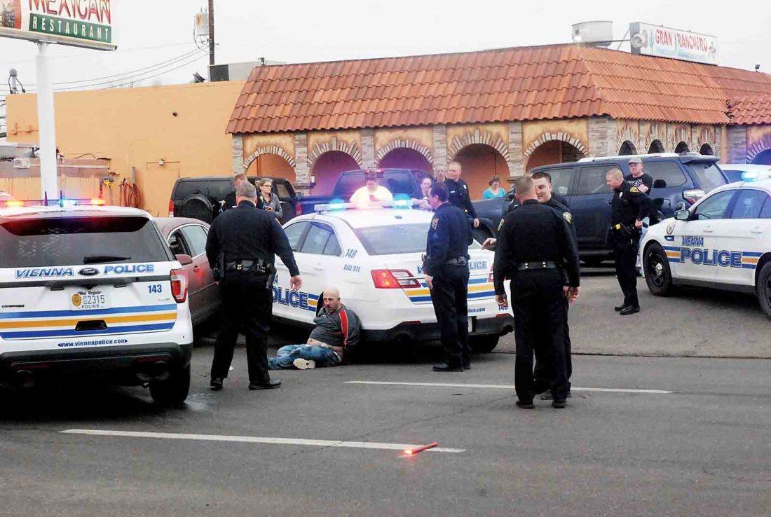 Photo by Evan Bevins Vienna and Parkersburg Police officers surround the scene where a reportedly stolen car was stopped by Vienna Police in front of Gran Ranchero Mexican Restaurant on Ohio Avenue in Parkersburg Thursday afternoon. A passenger in the car, Jason Bernard, is seen sitting against a Vienna cruiser. Bernard faces misdemeanor charges of fleeing and obstructing and was taken to Camden Clark Medical Center and later Ruby Memorial Hospital in Morgantown for injuries sustained when he was apprehended.