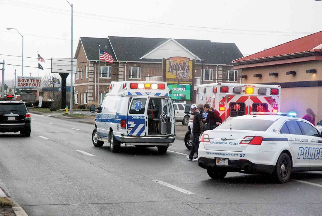 Photo by Evan Bevins Suspect Derick Walker, left, is escorted to an ambulance by law enforcement officers after being arrested on charges of fleeing in a vehicle with reckless indifference and receiving/transferring a stolen vehicle Thursday afternoon on Ohio Avenue in Parkersburg.