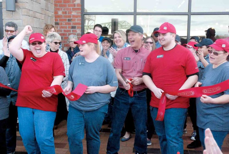 Photo by Evan Bevins Parkersburg Sheetz employees celebrate after manager Johnny Lewis, center, cut the ribbon at the 306 Ann St. store Thursday. Approximately 70 people are expected to be employed between the two stores.