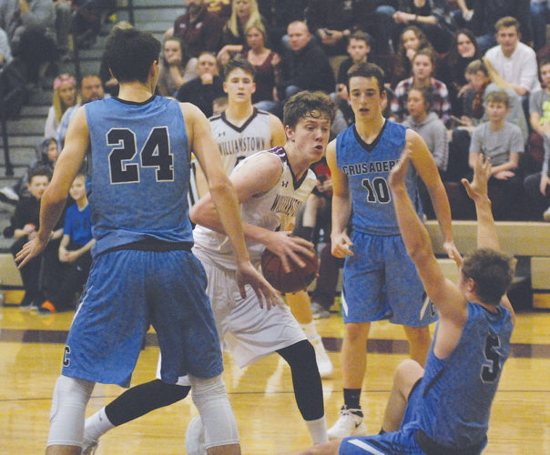 Williamstown's Cullen Cutright, center, gets called for an offensive foul on Parkersburg Catholic's Ty Sturm (5) during a high school boys basketball game Friday. Photo by Jordan Holland.