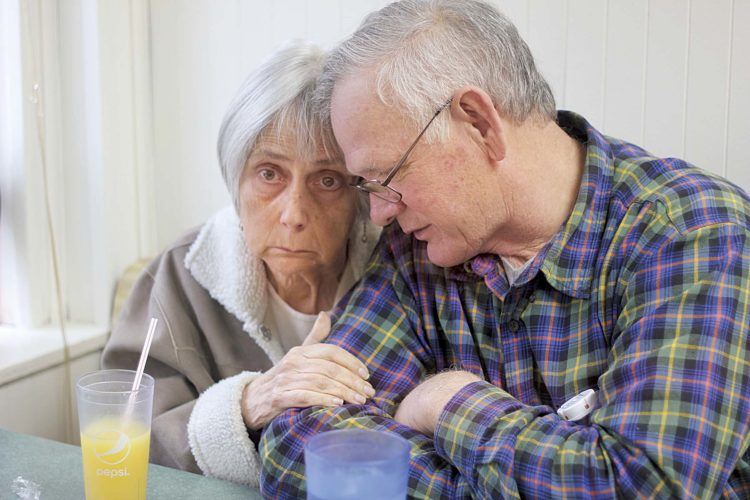 Photo by Janelle Patterson Karen Henderson clings to her husband Ted Henderson on Friday while at breakfast at the Busy Bee in Marietta. Ted has taken care of Karen for the last four years as her dementia has progressed into Alzheimer's.