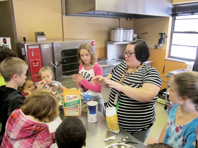 Kayla Lynch, center, teen director at the Boys and Girls Club of Parkersburg, leads boys and girls in a project to make homemade dog treats Monday at the club on Mary Street in Parkersburg. (Photo by Wayne Towner)