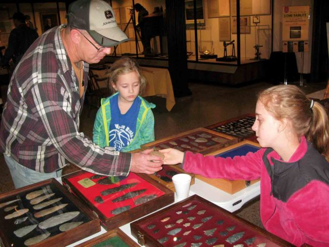 "File Photo Tim Glover, left, and his daughter Emily Glover, middle, look over a stone held by Kaylee Henry, right, of Waterford, during last year's ""Digging the Past: Archaeology Day"" at Campus Martius Museum."