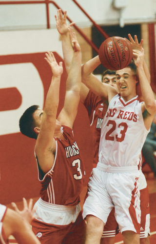 Parkersburg High's Gavin Dudley (23) tries to shoot against Hurricane's Michael Watson (33) in the host Big Reds' Class AAA 58-56 win over the No. 13-ranked Redskins Thursday night at Memorial Fieldhouse. Photo by Steve Hemmelgarn.
