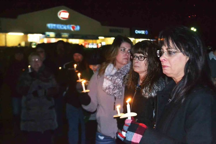 Photo by Michael Kelly Lenora Lada, mother of Trey Moats, and about 30 of Moats' friends and family gathered Friday night to hold a vigil on what would have been his 27th birthday. He died of a drug overdose Dec. 2. A billboard overlooking the site of the vigil urges people to become familiar with the Good Samaritan law.