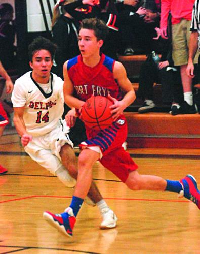 Photo by Steve Hemmelgarn Fort Frye's Kelton Fogle, right, looks to pass as Belpre's Logan Adams defends during a high school boys basketball game Saturday.