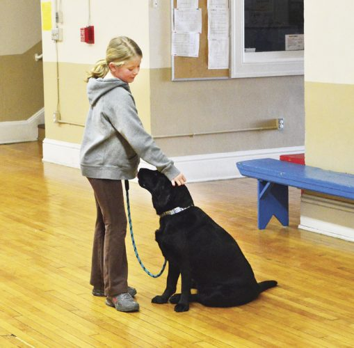 Photo by Doug Loyer Sophia Linscott, 10, of Marietta, pats her dog Olive, a Black English Labrador, on the head after completing a trick.