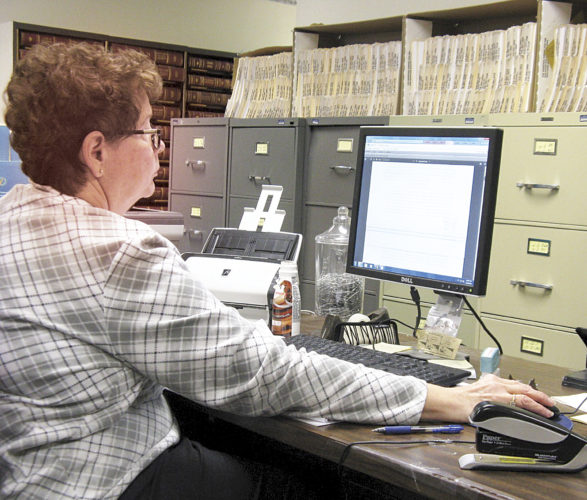 Photo by Jeffrey Saulton Andrea Weaver, an employee in the Wood County Circuit Court Clerk's Office, reviews a document she scanned into the court's Courtplus scanning system.