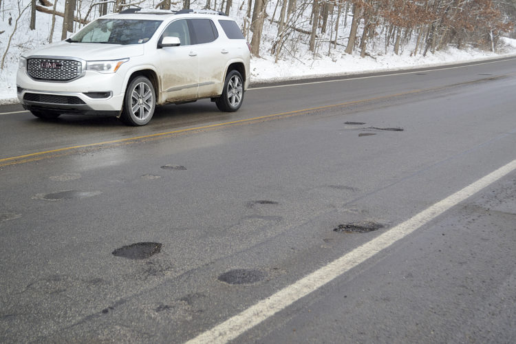 Photo by Erin O'Neill Drivers try to navigate potholes and loose gravel on Ohio 60. Several complaints have been made to ODOT regarding damage done to people's vehicles when driving through the state's microsurfacing project that stretches from Devola to the Morgan County line.