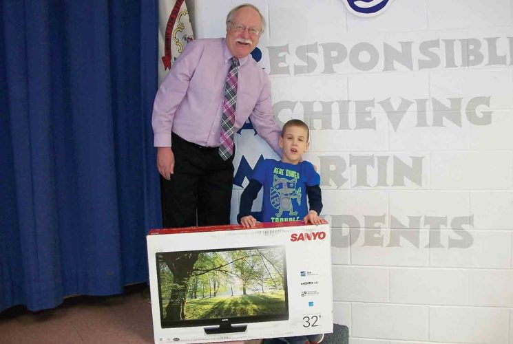 Wood County Board of Education member Ron Tice stands with Martin Elementary School first-grader Emery Robinson, who last week was presented with a 32-inch television after his name was drawn from a pool of students recognized for good attendance. Tice donated the television, as well as gift cards for weekly attendance drawings. (Photo Provided)